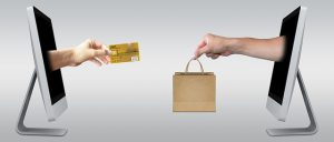 two facing computers one with credit card prortruding and the other with a shopping bag
