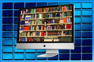 library of books on computer monitor