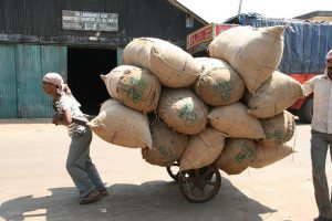 small man pulling enormous load of sacks
