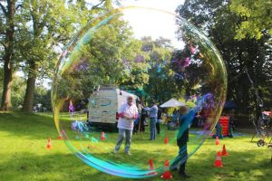 family playing soap bubbles outdoors