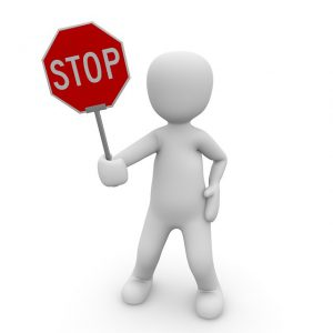 small figure holding stop sign